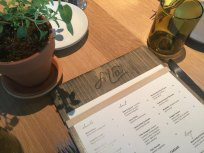 Menu presentation on a wood board, just one of the details Fi'lia is made of.