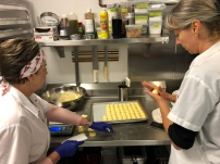Maria and Myrtille weighing, portioning and rolling one of several dozen cheesy yuca puff trays to prepare for a busy weekend. When all is said and done, they'll go through about 600.